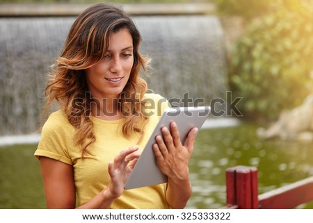 Cheerful lady in yellow shirt browsing internet on tablet outdoors - focus on foreground - stock photo