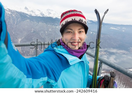 Cheerful lady taking selfie enjoing the snowy mountain view, excited before skiing. - stock photo