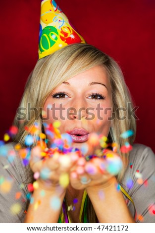 Cheerful lifestyle party celebrating girl with blowing confetti to camera - stock photo