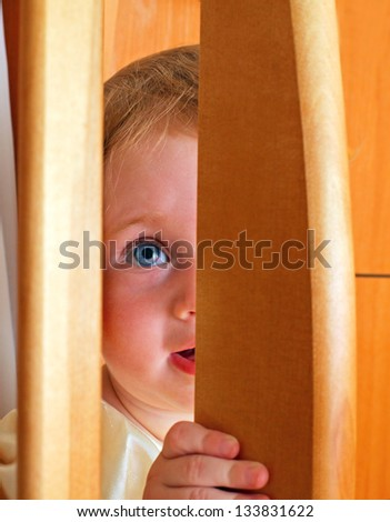 Cheerful Little Baby Playing Hide and Seek - stock photo