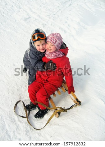 cheerful little boy and girl are laughing and hugging in the snow in winter outdoors - stock photo