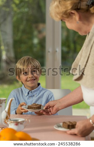 Cheerful little boy and his granny's tasty cookie - stock photo