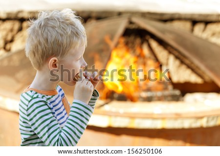 cheerful little boy eating smores by fire - stock photo