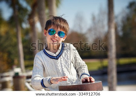 Cheerful little boy having relax outdoors during his summer vacation - stock photo
