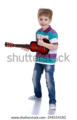 Cheerful little boy in jeans and a striped t-shirt strumming the guitar well, the boy is studying in a music school-Isolated on white background