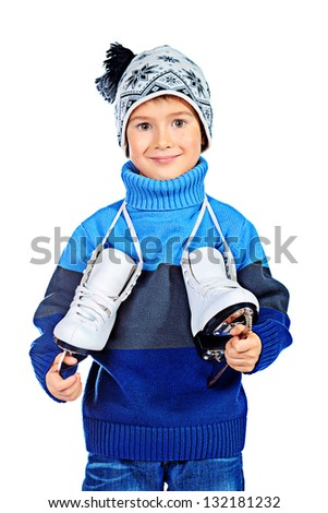 Cheerful little boy in warm sweater and hat  holding figure skates. Isolated over white background - stock photo