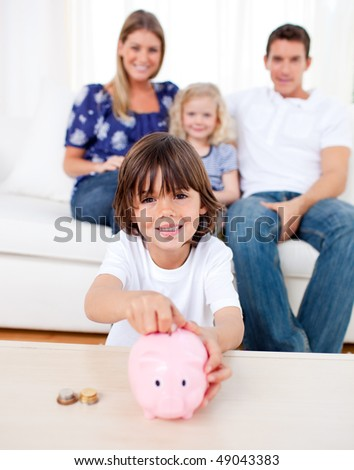Cheerful little boy inserting coin in a piggybank in the living room