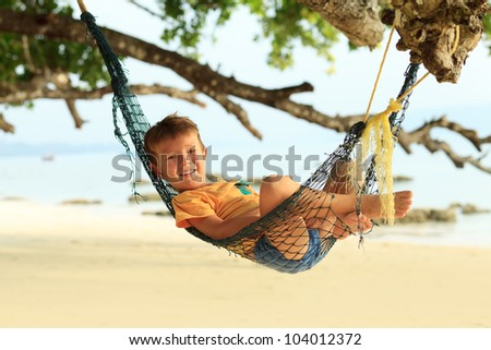 Cheerful little boy playing on a beach. Tropical getaway. - stock photo