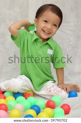 Cheerful little boy playing with balls - stock photo
