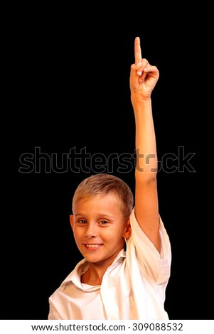 Cheerful little boy pointing up isolated on black background - stock photo
