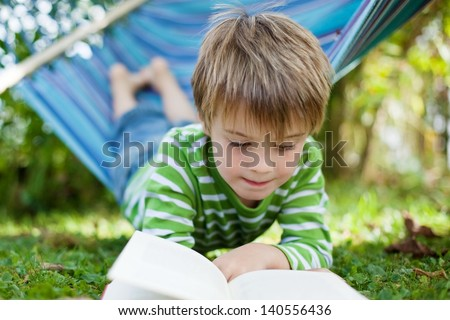 Cheerful little boy reading book lying on the hammock - stock photo