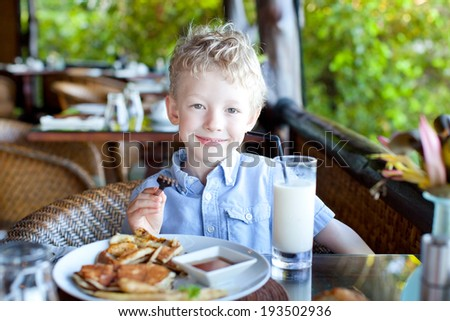 cheerful little boy ready for his breakfast at the resort - stock photo