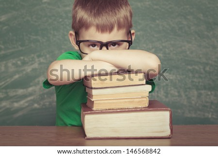 Cheerful  little boy sitting at the table. Looking at camera School concept - stock photo