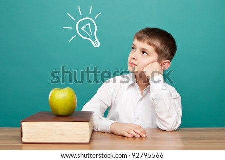 cheerful  little boy sitting at the table. School concept - stock photo