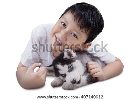 Cheerful little boy with siberian husky puppy lying down in the studio and smiling at the camera, isolated on white background