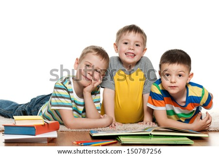 Cheerful little boys are lying on the floor and reading - stock photo