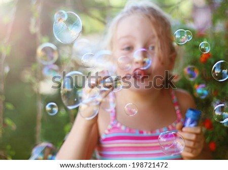 Cheerful little girl blows soap bubbles outdoor in summer - stock photo