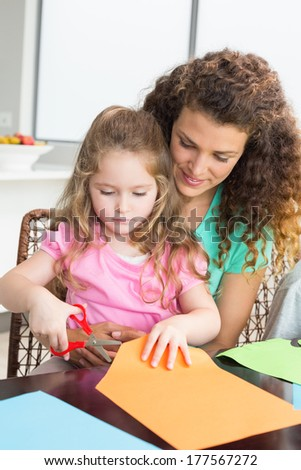 Cheerful little girl cutting paper with mother at the table at home in kitchen - stock photo
