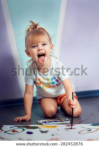 cheerful little girl draws at home paints and builds funny faces - stock photo