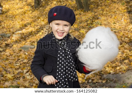 Cheerful little girl eating cotton candy - stock photo