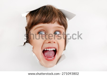 Cheerful Little Girl Face through the Hole of the White Paper - stock photo