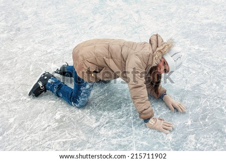 Cheerful little girl fallen while skating on the ice in winter - stock photo