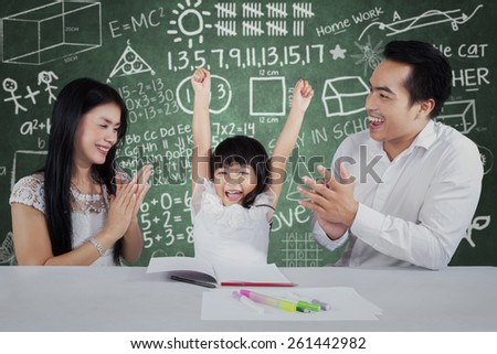 Cheerful little girl get appreciation and applause from her parents after studying - stock photo