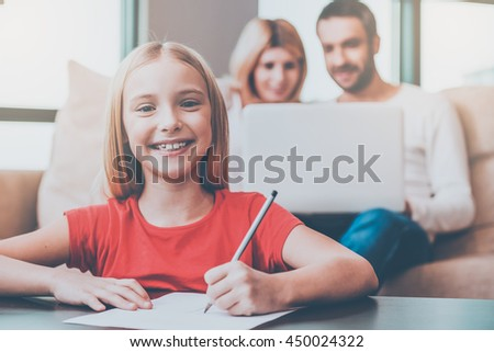 Cheerful little girl. Happy little girl drawing something on paper and smiling while her parents sitting in the background with laptop