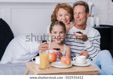 Cheerful little girl holding berry cupcakes with her grandparents