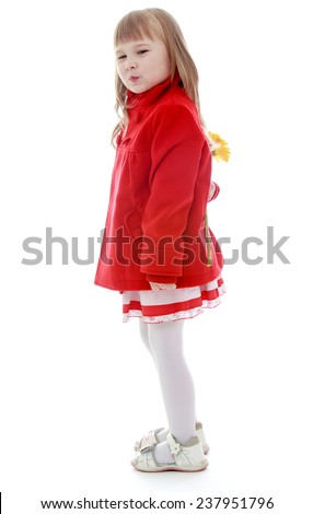 Cheerful little girl in red coat holds behind his back a beautiful yellow flower.Happy childhood, fashion, autumnal mood concept. Isolated on white background - stock photo
