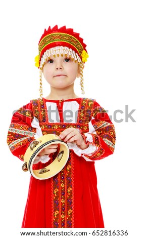 Cheerful little girl in Russian folk dress. The girl hits the drum.Isolated on white background.