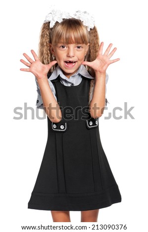 Cheerful little girl in school uniform, isolated on white background - stock photo