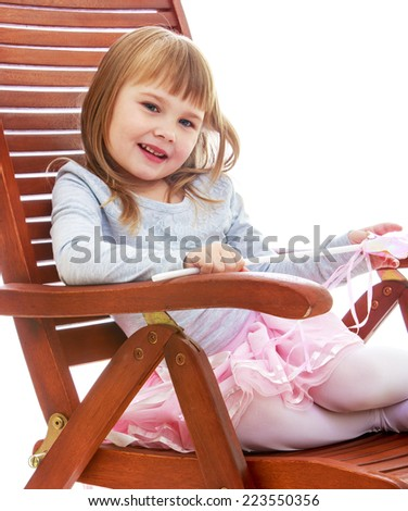cheerful little girl is resting on a large wooden chair. Happy childhood, fashion, autumnal mood concept. Isolated on white background - stock photo