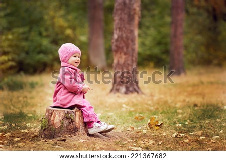 Cheerful little girl on a stump in the woods of autumn