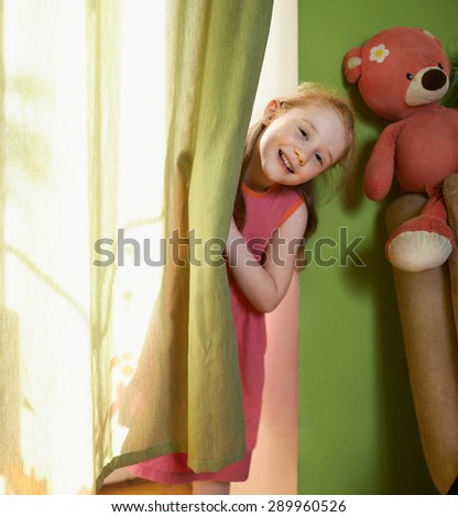 cheerful little girl peeking out from behind the curtains - stock photo