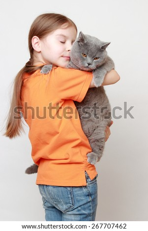 Cheerful little girl played with a British breed of cat - stock photo