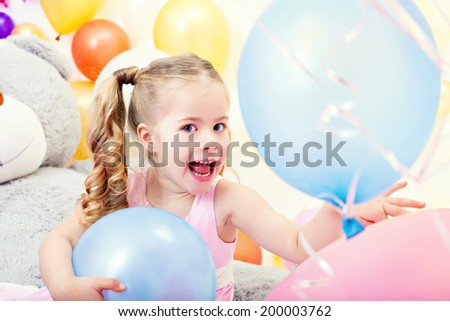 Cheerful little girl posing with blue balloons
