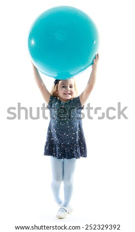 Cheerful little girl raised her head above the big blue ball.Isolated on white background, Lotus Children's Center. - stock photo