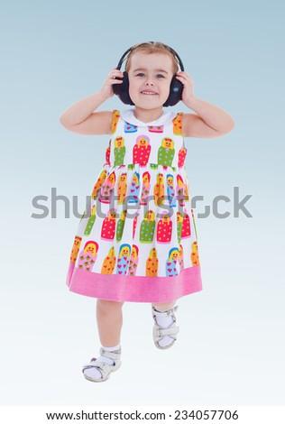 Cheerful little girl running around in big black headphones music. - stock photo