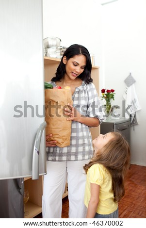 Cheerful little girl unpacking grocery bag with her mother in the kitchen - stock photo