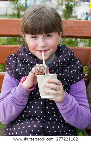 cheerful little girl with a drink on a park bench - stock photo