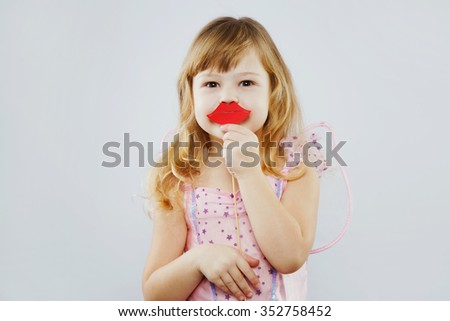 Cheerful little girl, with curly blond hair, wearing on pink dress, and wings on her back, posing with red paper lips and looking at camera, on white background, in studio, waist up - stock photo