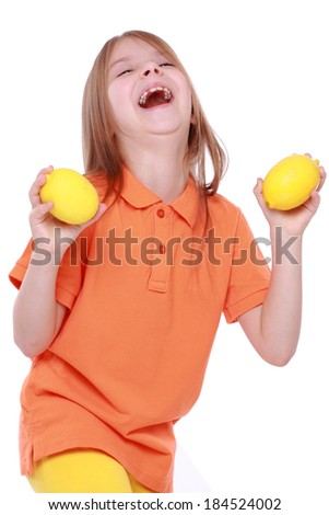 cheerful little girl with lemons - stock photo