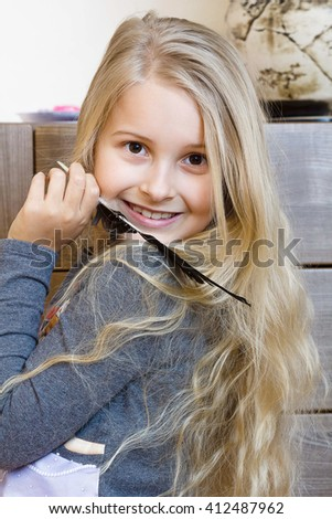 Cheerful little girl with long blond hair with a bird's feather - stock photo