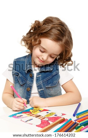 Cheerful little girl with sketch pen drawing in kindergarten.