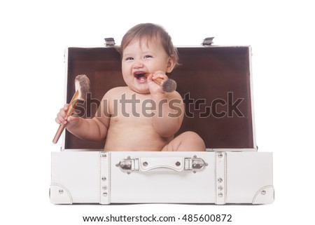 Cheerful little girl with two make-up brushes sitting in a suitcase on isolated white