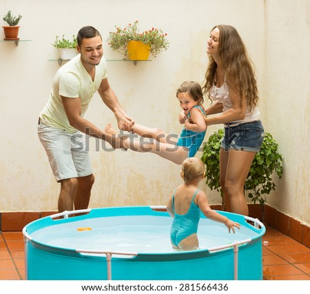 Cheerful little girls with happy parents having fun in pool at terrace. Focus on girl