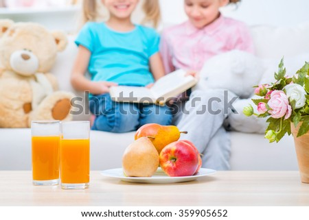 Cheerful little sisters sitting on the sofa  - stock photo