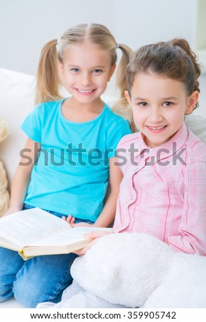 Cheerful little sisters sitting on the sofa