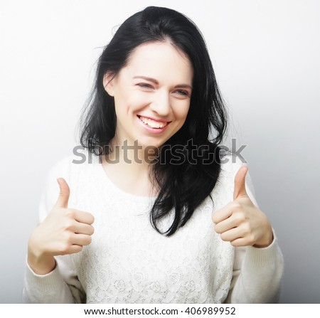 Cheerful lovely girl showing thumbs up  - stock photo